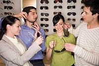 Two couples shopping for sunglasses in store