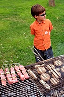 Boy standing near a barbecue