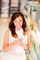 Shopping _ smiling woman holding moisturizer in supermarket