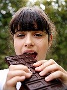Young teenage girl eating chocolate