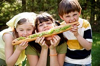 Three children sharing a large sandwich