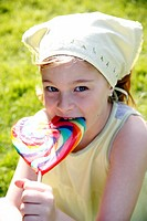 Young girl licking a lollipop