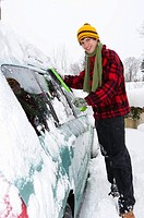 Austria, Young man cleaning snow on car