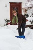 Austria, Young man shoveling snow in front of house, portrait