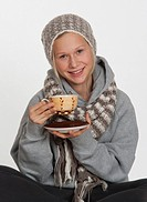 Teenage girl with tea cup, smiling, portrait
