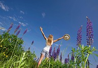 Austria, Teenage girl standing in lupine field
