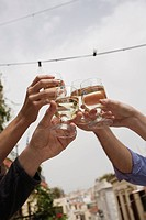 People's hands toasting with white wine