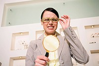 Woman with magnifying glass in store