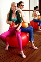 Two young women on exercise ball taking a break