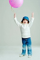 An image of a little girl in a hat and white jumper with balloon