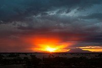 Sunset at Amboseli: dramatic red orange yellow against stormy grey clouds, over distant mountain, sandy plains and trees in foreground, Amboseli, Keny...
