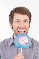 Mid adult man eating lollipop, portrait