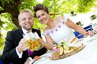 Bridal couple having a light meal and drinking beer in a Bavarian beer garden, Regensburg, Bavaria, Germany, Europe