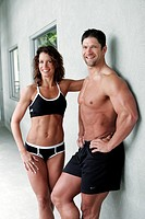 fit couple in bathing suits posing ouside