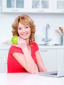 Portrait of happy smiling woman with green apple sitting in the kitchen
