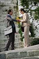 Businessman giving businesswoman flowers