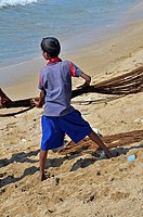 Young fisherman, 10, pulling in a net on a beach in Galle, Sri Lanka, Ceylon, South Asia, Asia