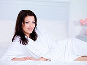 Beautiful woman with attractive smile relaxing on a bed at home _ indoors