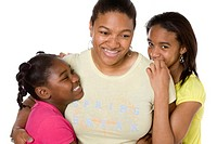 Studio portrait of African American mother and daughters smiling and hugging on white background