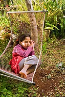 little girl sleeping in a hammock with a book