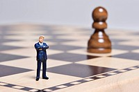 Business figurine on a chess board with a pawn chess piece.