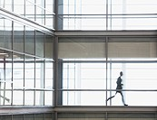 Businessman running along corridor in office