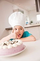 Little girl with chef's hat nibbling on a creampie