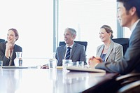 Smiling business people sitting at conference room table
