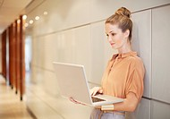 Businesswoman using laptop in corridor (thumbnail)