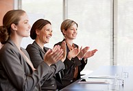 Businesswomen clapping in conference room