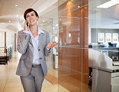 Smiling businesswoman talking on cell phone in office corridor (thumbnail)