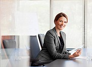 Portrait of smiling businesswoman with digital tablet in conference room (thumbnail)