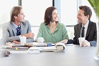 Business people with coffee talking at table in conference room (thumbnail)
