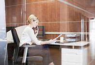 Businesswoman talking on telephone at desk in office