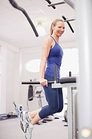 Smiling woman on dip machine in gymnasium (thumbnail)