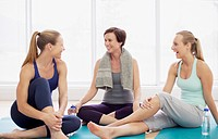 Smiling women resting on exercise mats