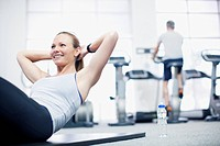 Smiling woman doing sit-ups in gymnasium (thumbnail)