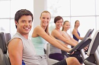 Portrait of smiling people on exercise bikes in gymnasium