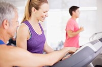Man guiding woman on treadmill