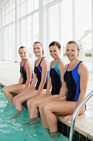 Portrait of smiling swimmers with feet in swimming pool
