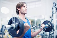 Man lifting barbell in gymnasium