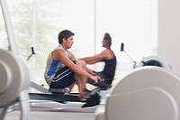Men exercising on rowing machines in gymnasium