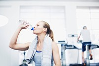 Woman with towel around neck drinking water in gymnasium