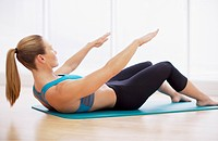 Woman doing crunches on exercise mat in fitness studio