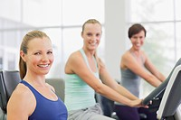 Portrait of smiling women on exercise bikes in gymnasium