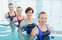 Portrait of smiling women in a row in swimming pool