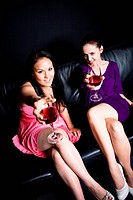 Two beautiful women drinking and toasting wine at a party in a club