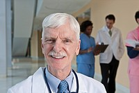 Doctor smiling with his colleagues in the background