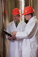 Two scientists making reports in a chemical plant