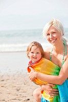 Cheerful girl in a towel and her smiling mother playing on the beach during summer